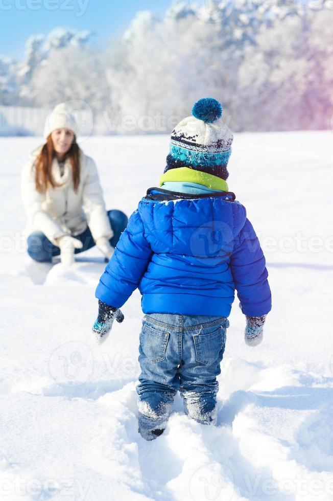 babyboy son och mamma är glada tillsammans, vinter snöig dag foto