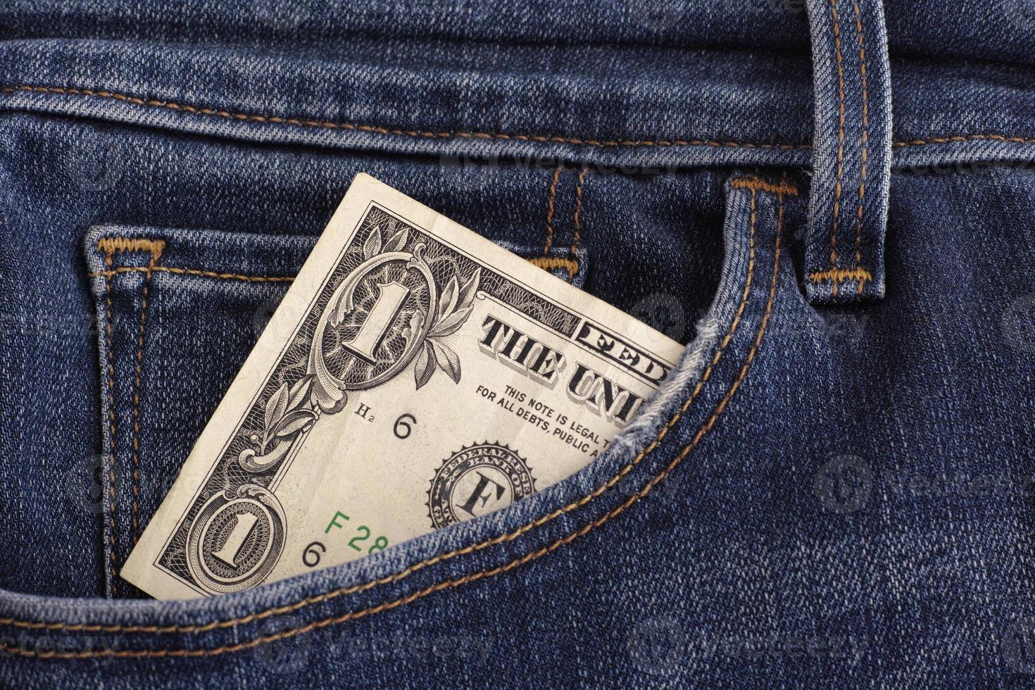 en dollarräkning i en ficka med blå jeans foto