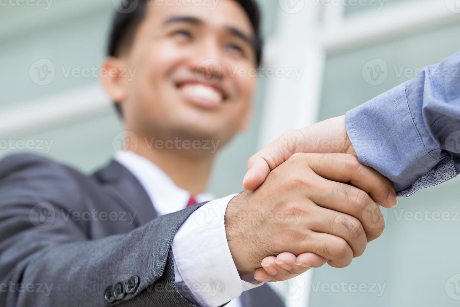 asiatisk affärsman som gör handskakning med leende ansikte foto