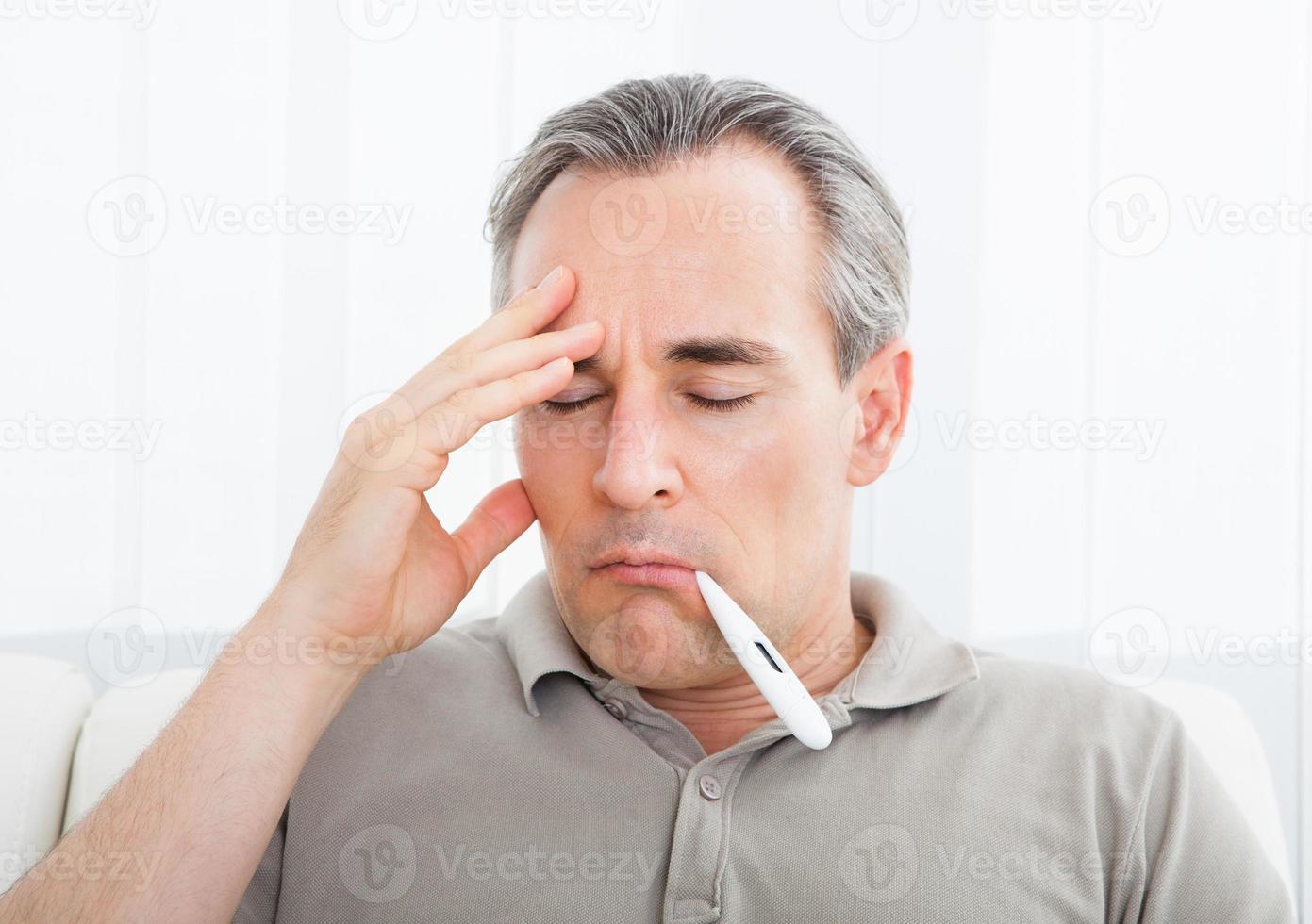 mogen sjuk man med en termometer i munnen foto