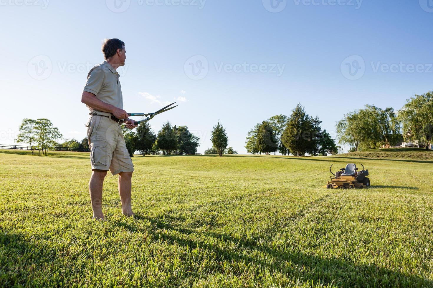 äldre man skär gräs med sax foto