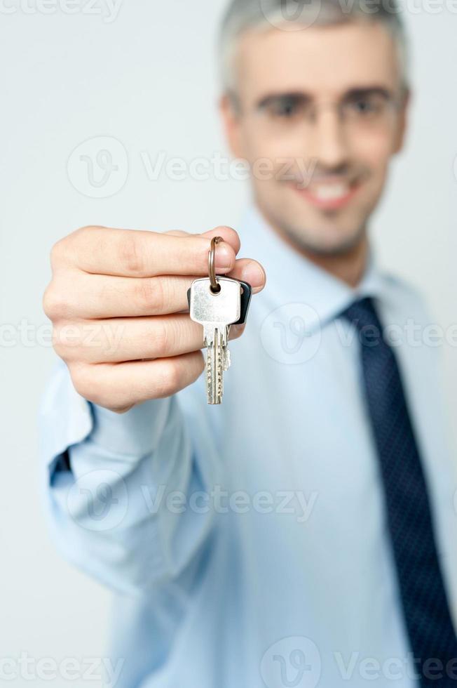 ung fastighetsmäklare som erbjuder husnyckel foto