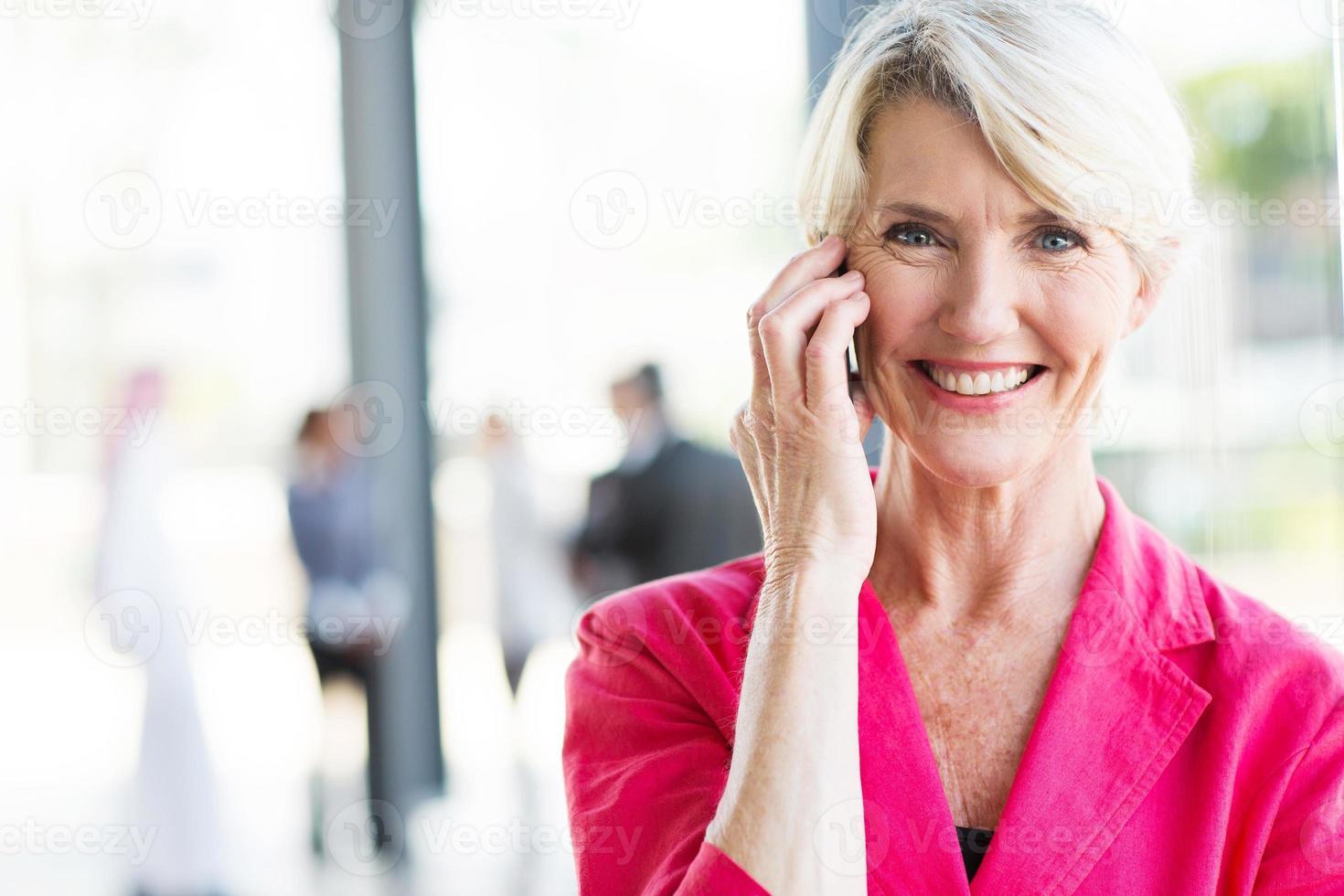 äldre affärskvinna talar i mobiltelefon foto