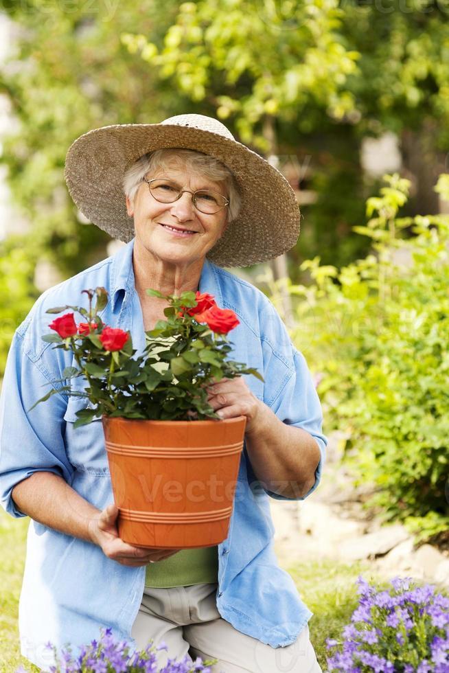 äldre kvinna med blommor i trädgården foto