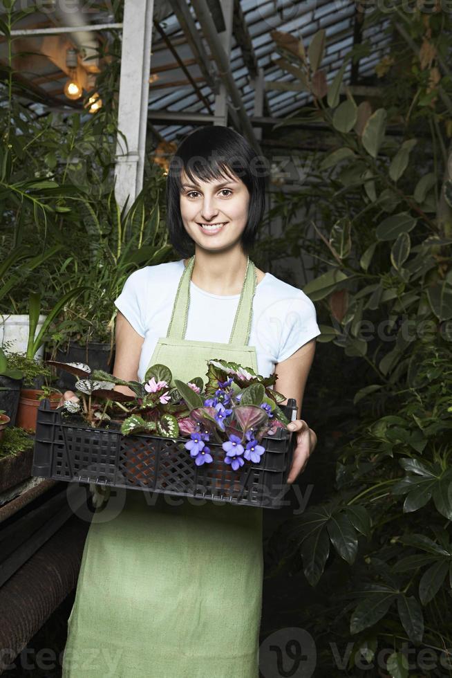 kvinnlig botaniker som bär korg full av blommor foto