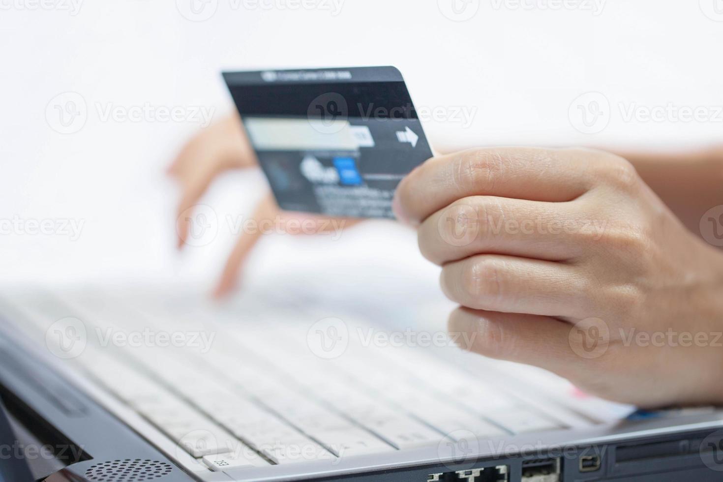 med ett kreditkort. foto