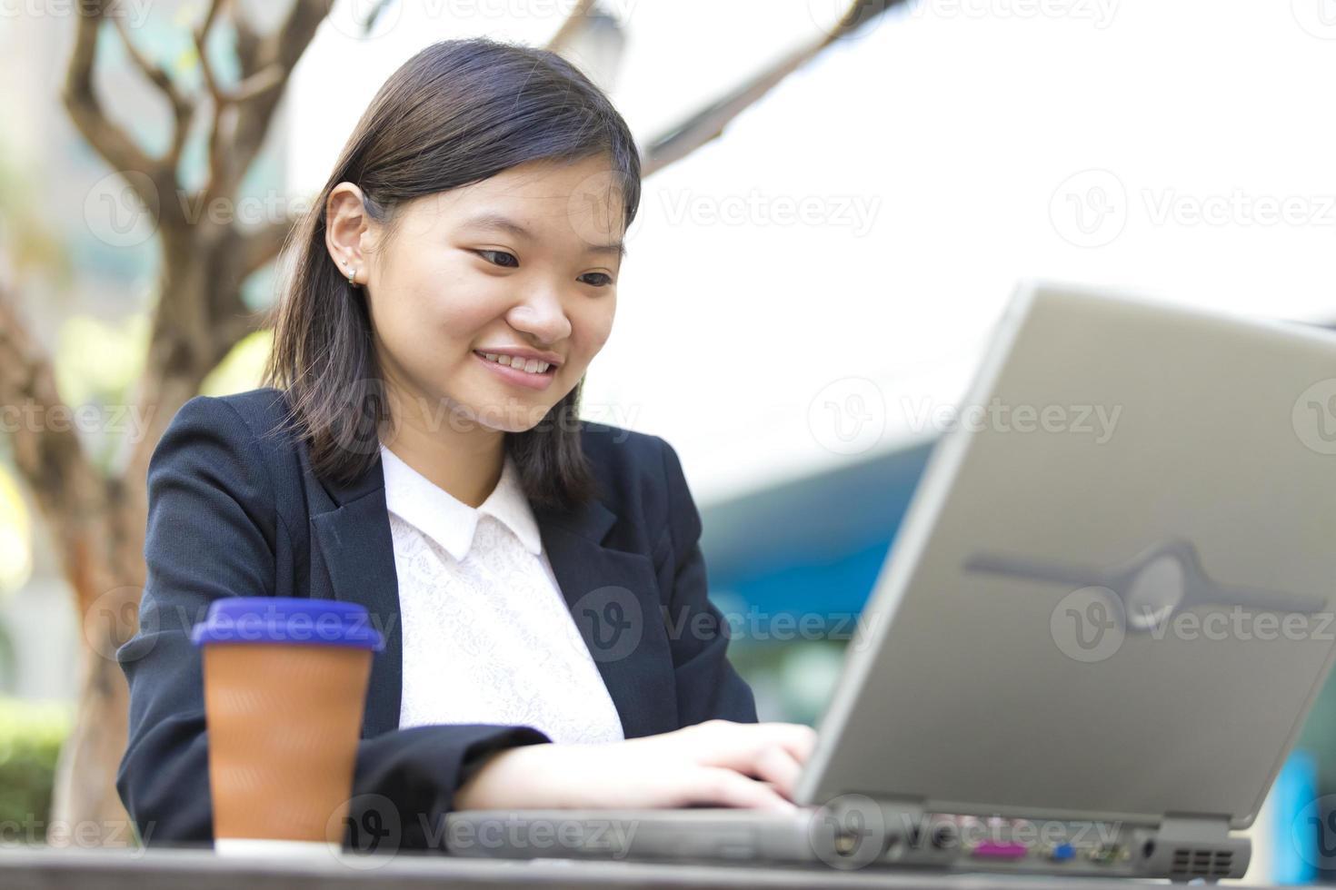 ung kvinnlig asiatisk företagsledare som använder bärbar dator foto