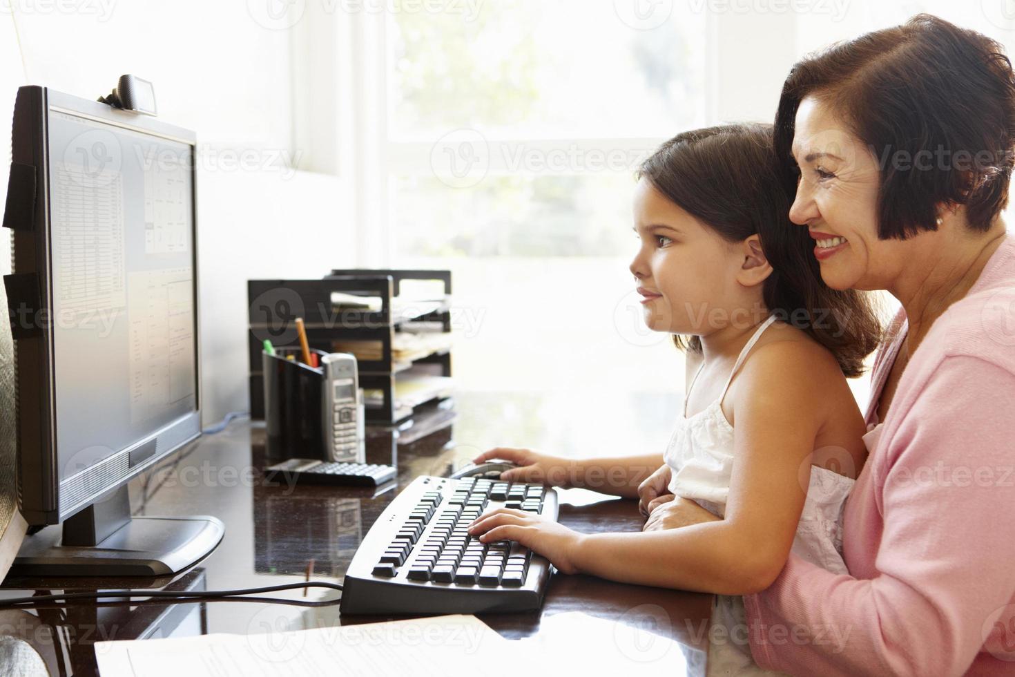 senior latinamerikansk kvinna med dator och barnbarn foto