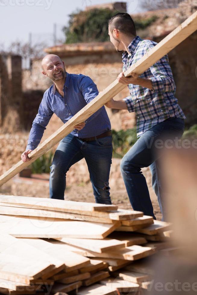 arbetare som ordnar byggnadsvirke på gården foto