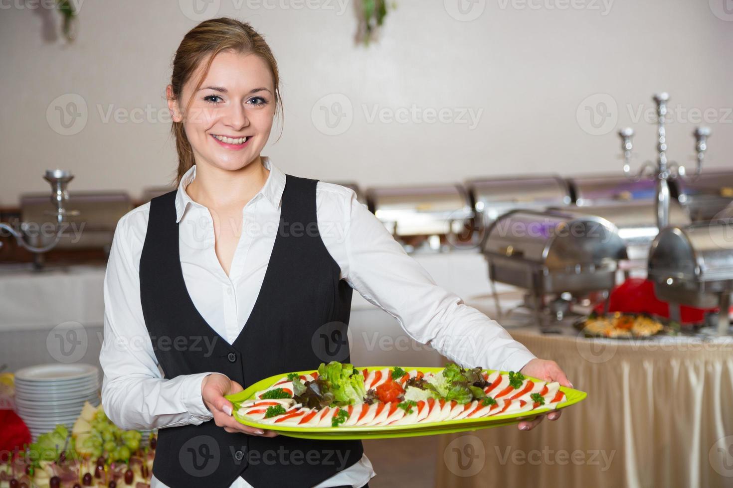 cateringtjänstmedarbetare som poserar med bricka för buffett foto