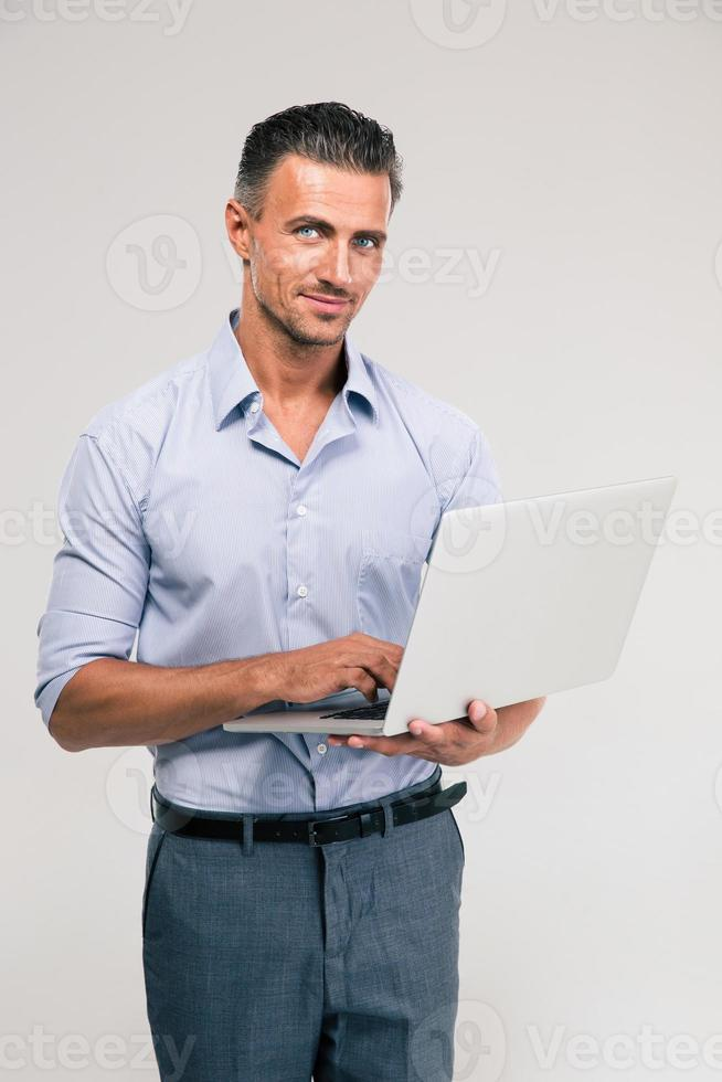 porträtt av en lycklig affärsman som använder bärbar dator foto