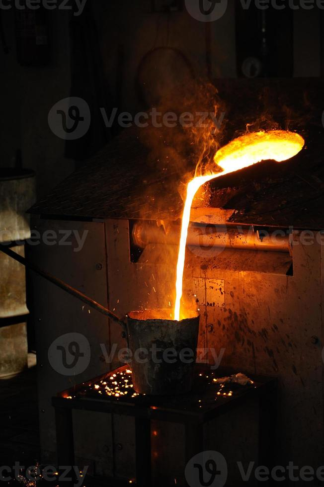 gjuteri - smält metall som hälls från svarven för gjutning foto