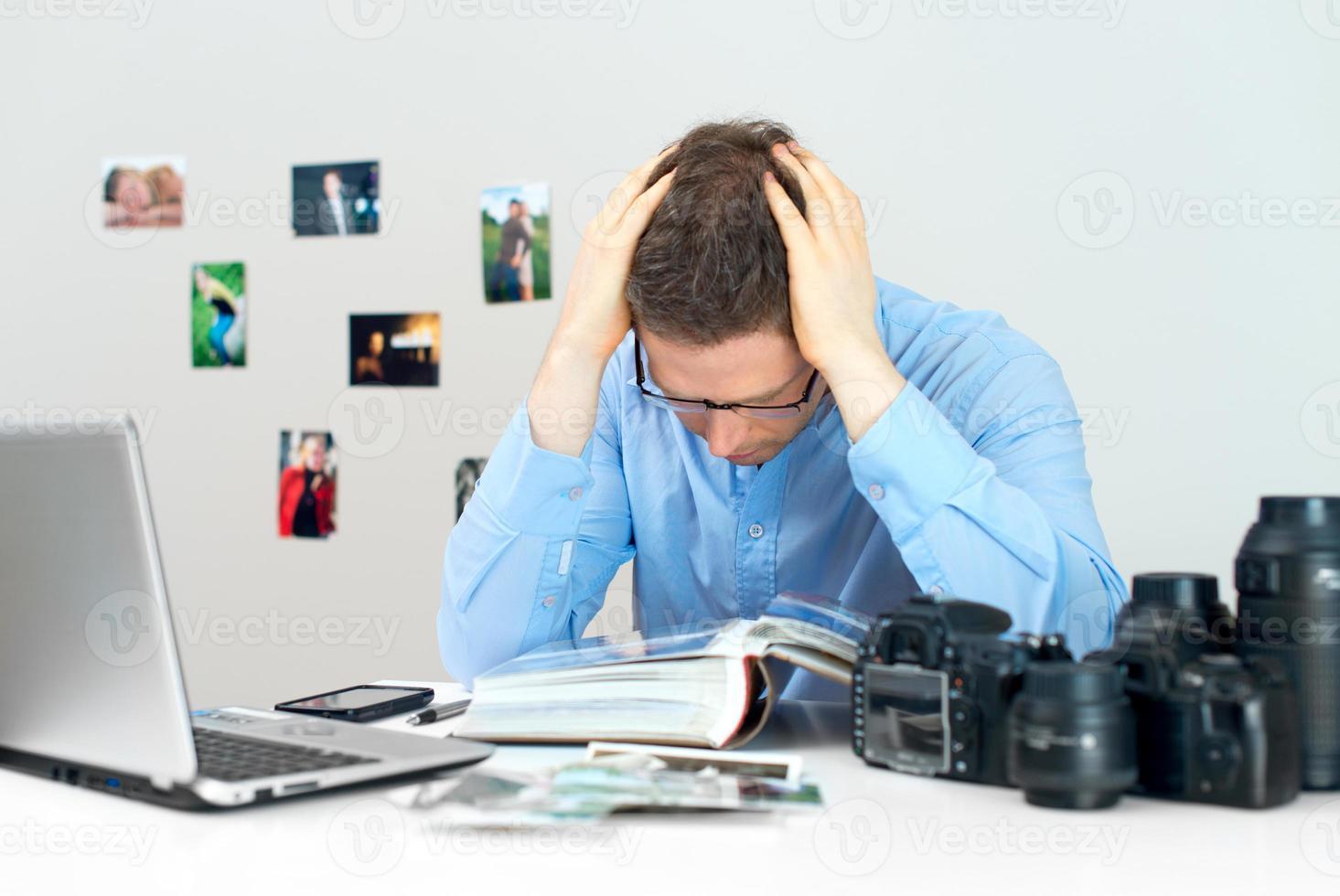 trött fotograf som arbetar på sin arbetsplats. foto