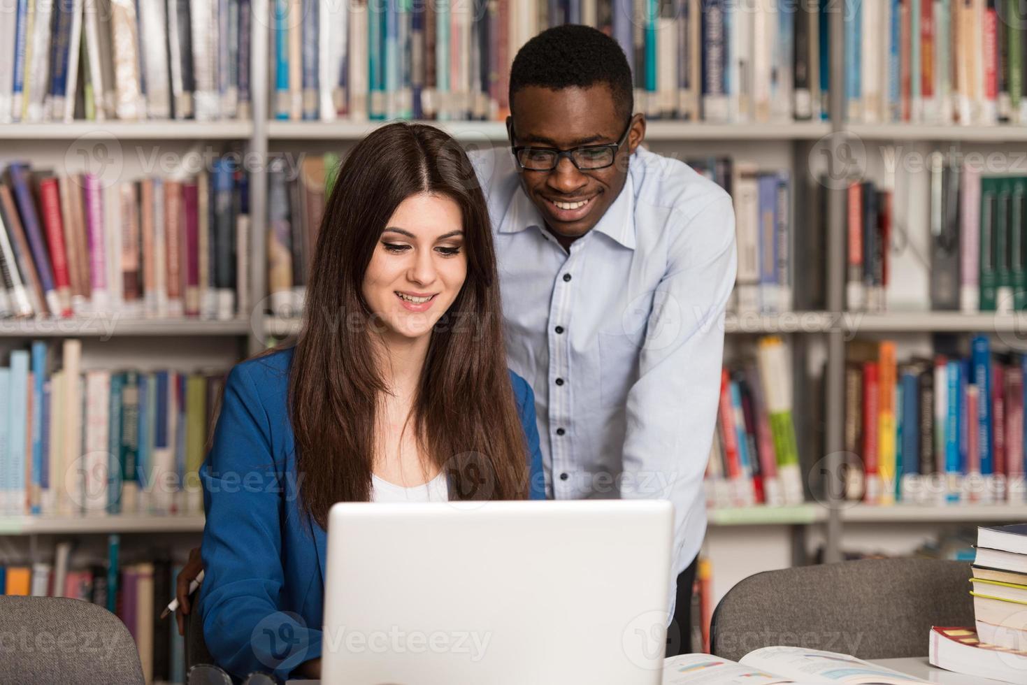 par studenter med bärbar dator i biblioteket foto