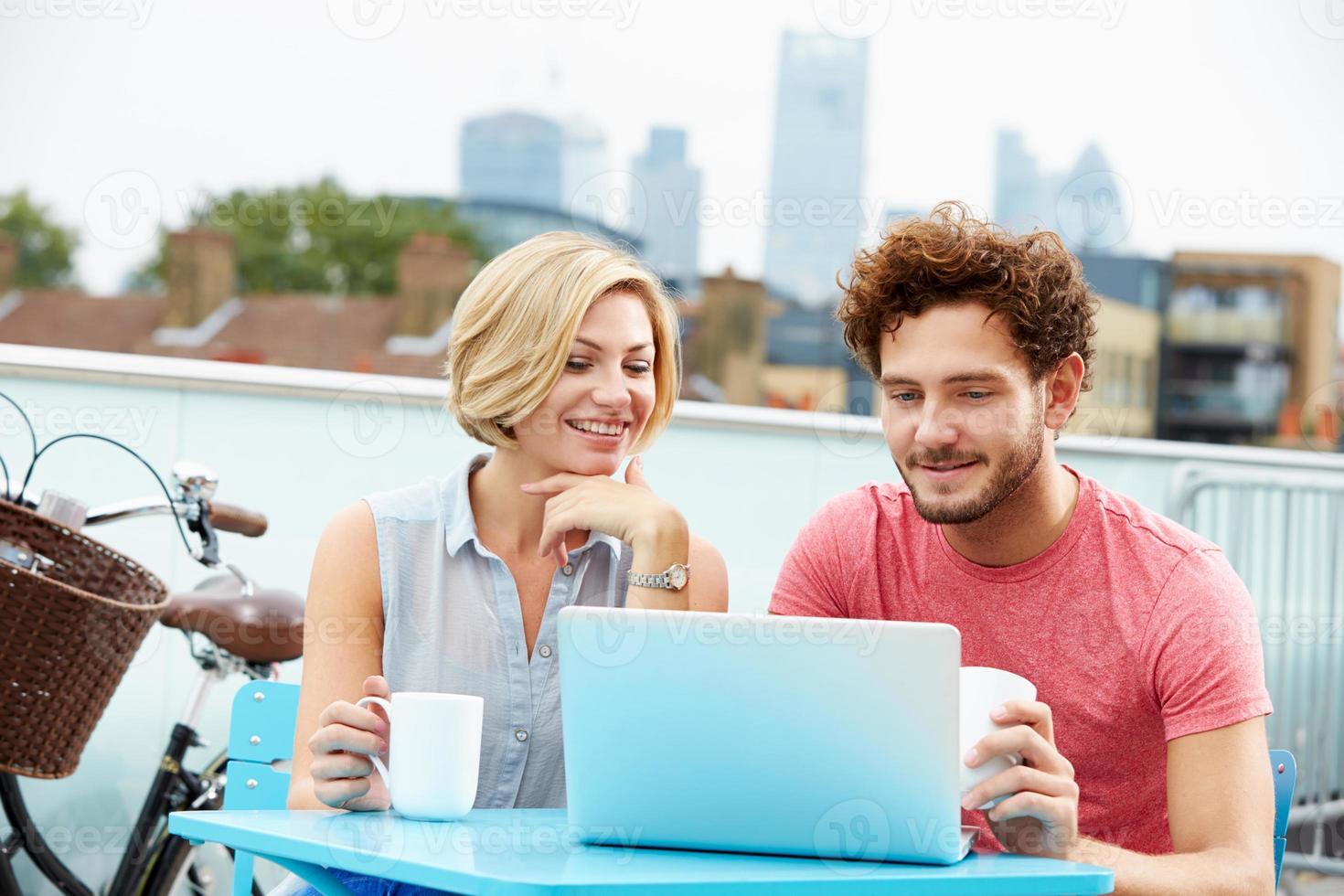 unga par som sitter på takterrassen med laptop foto