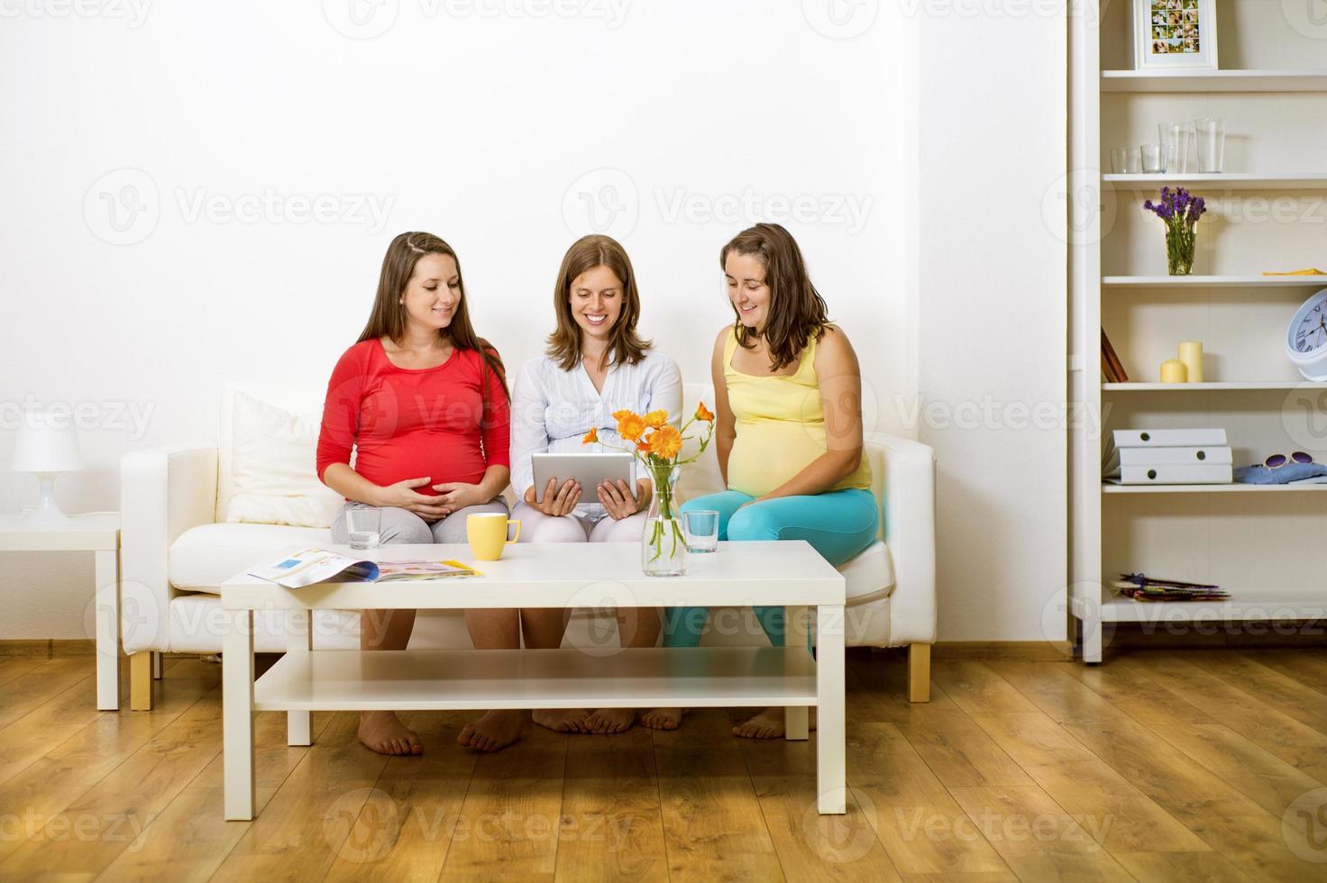 gravida kvinnor på soffan foto