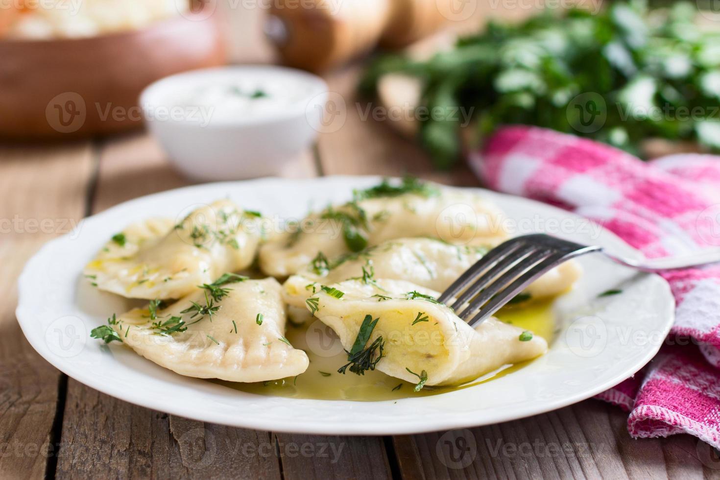 potatisfylld varenyky på en vit platta på träbord foto