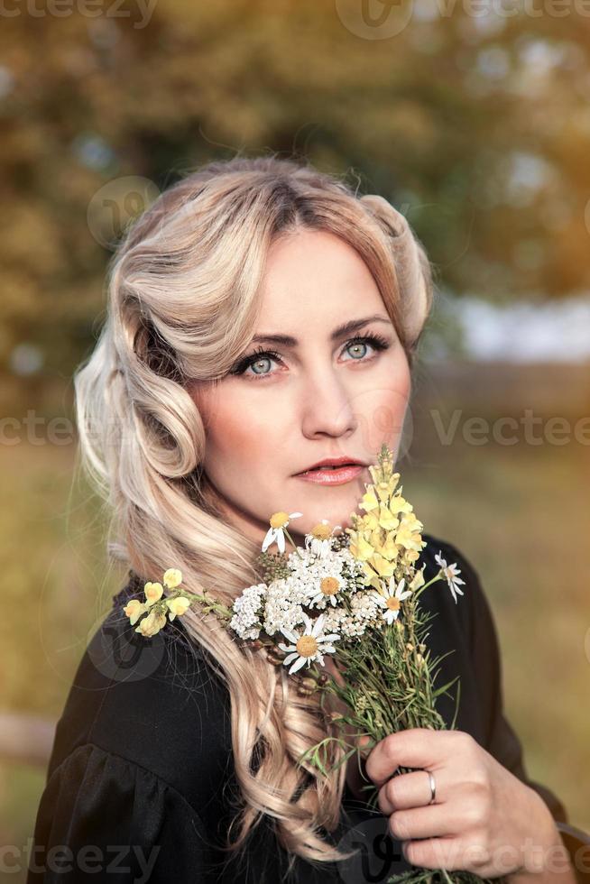 vacker blond kvinna i svart klänning i sommardag, utomhus foto