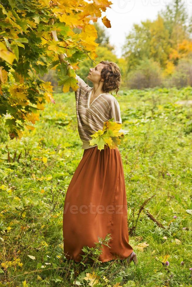 ung vacker kvinna som samlar höstlönnlöv foto