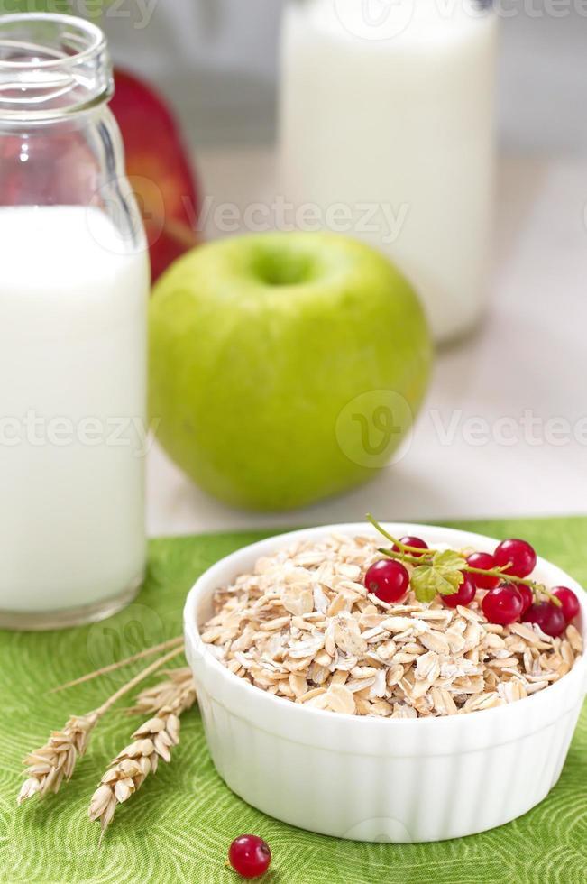 havremjöl med röda vinbär, mjölk och äpplen till frukost foto