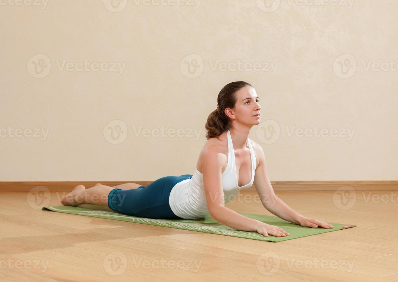 kaukasisk kvinna utövar yoga i studion (bkhudzhangasana) foto