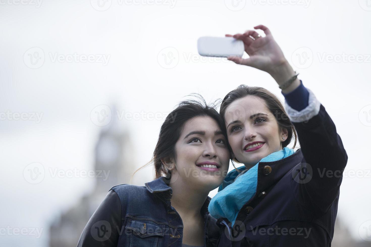 kaukasiska och kinesiska vänner som tar foto med telefonen.