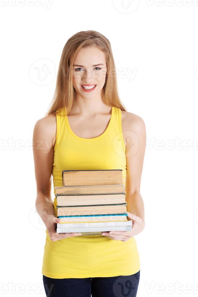 vacker avslappnad kaukasisk kvinna student håller bunt med böcker. foto