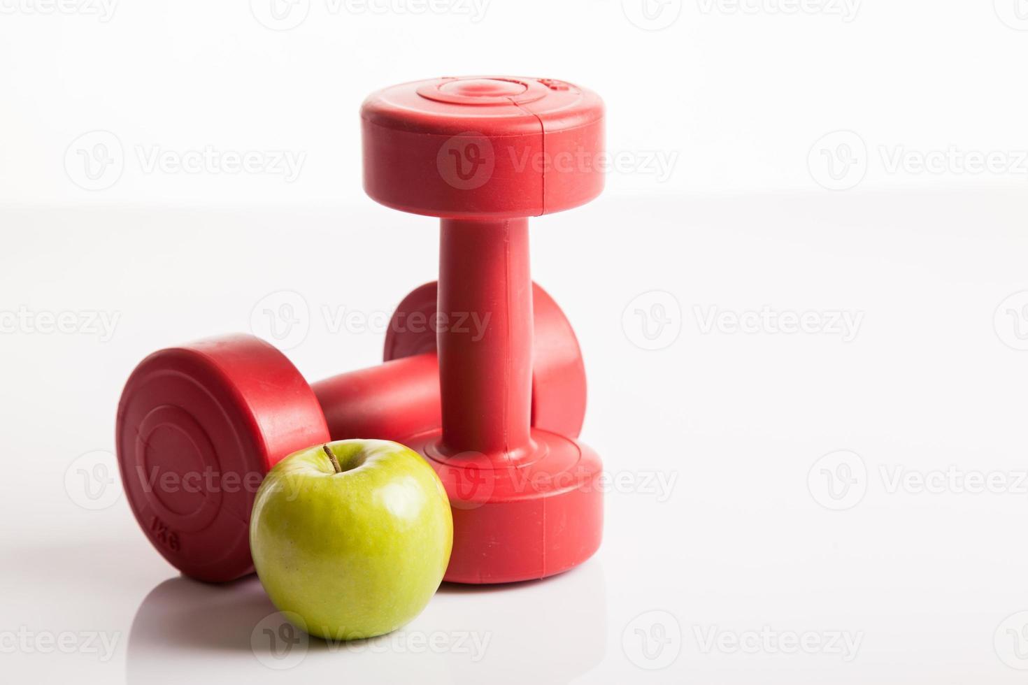 röda hantlar vikt med grönt äpple foto