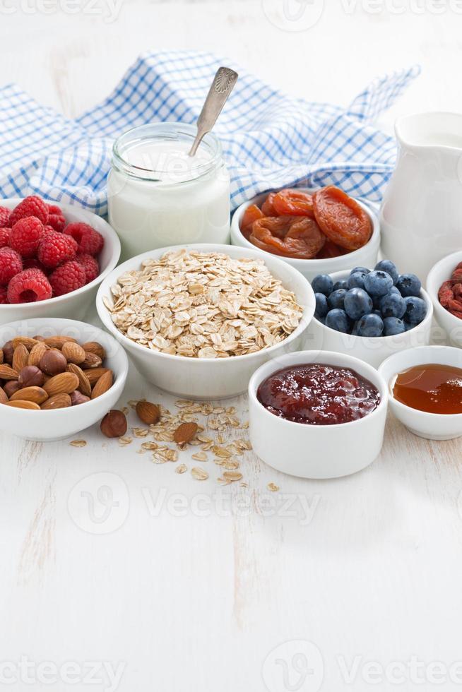 havreflingor och olika ingredienser till frukost på det vita bordet foto