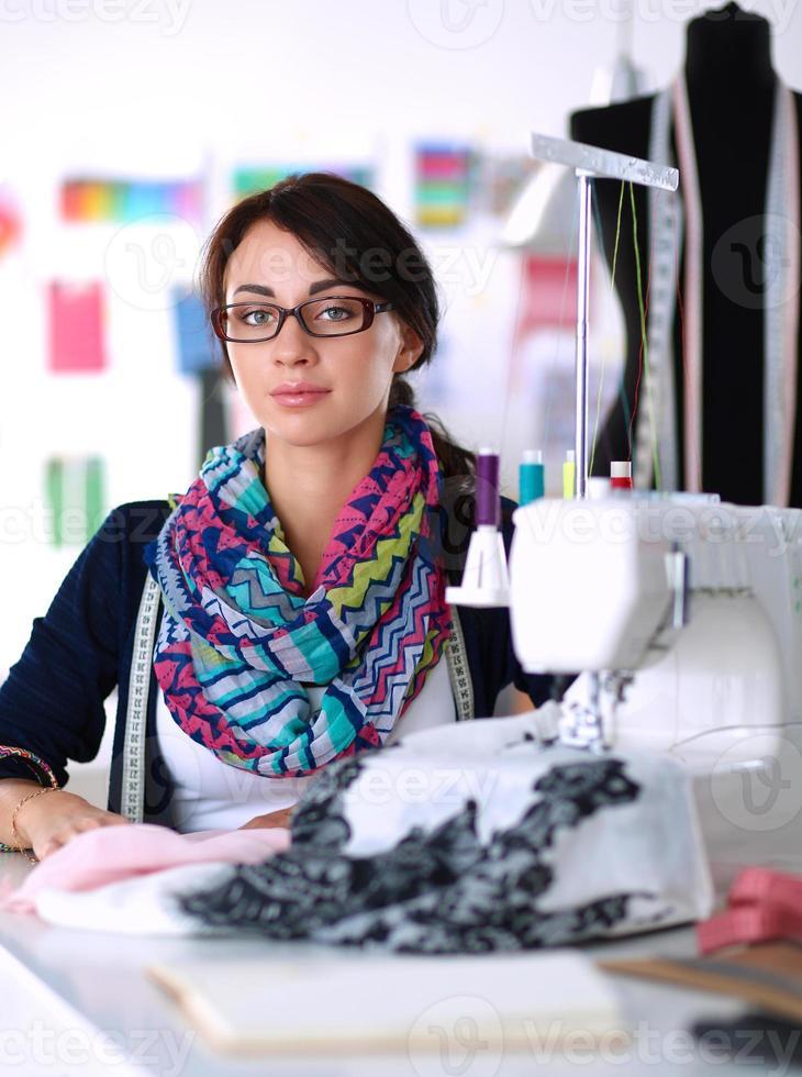 ung kvinna som sy medan hon sitter på sin arbetsplats foto