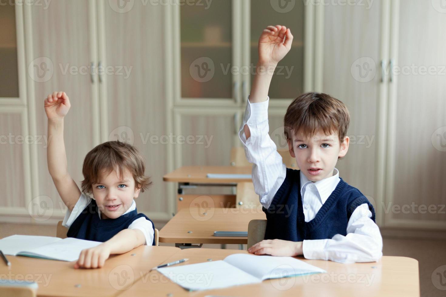 flitig student som sitter vid skrivbordet, klassrummet foto