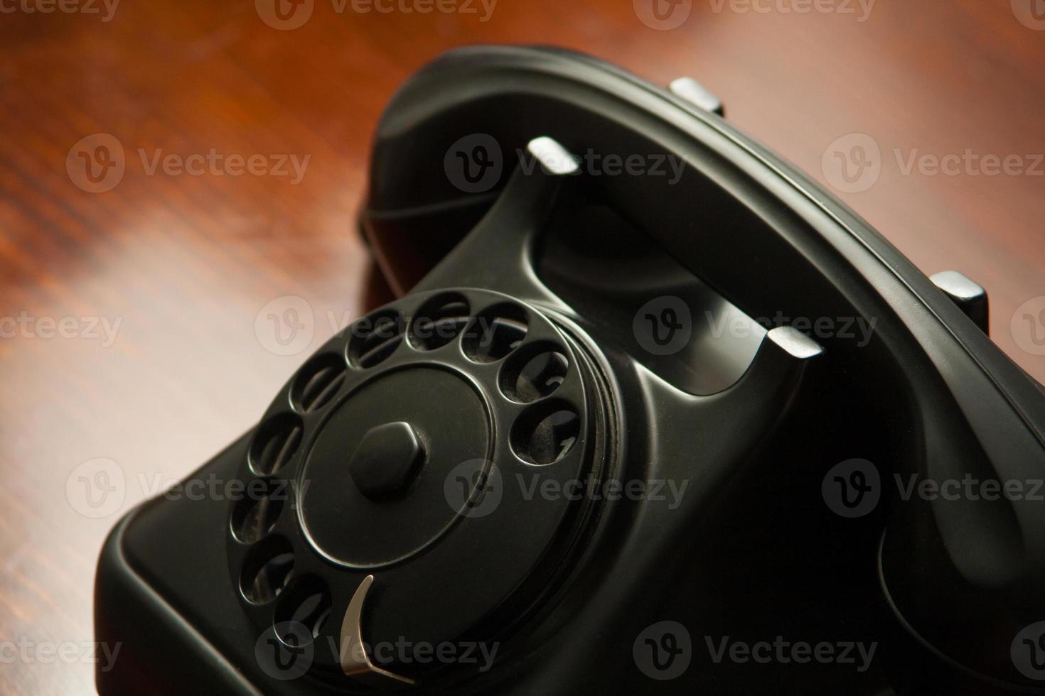 gammal retro svart telefon med rund urtavla på träskrivbord foto
