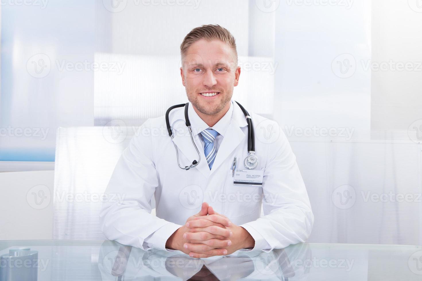 leende läkare eller konsult som sitter vid ett skrivbord foto