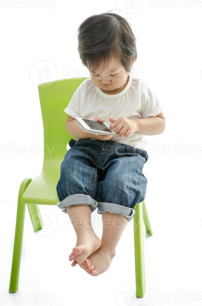 liten asiatisk pojke med smart telefon foto
