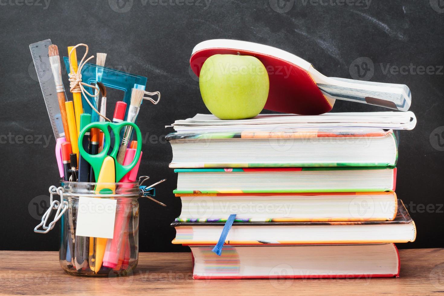 skoltillbehör på skrivbordet med svart tavla i bakgrunden foto