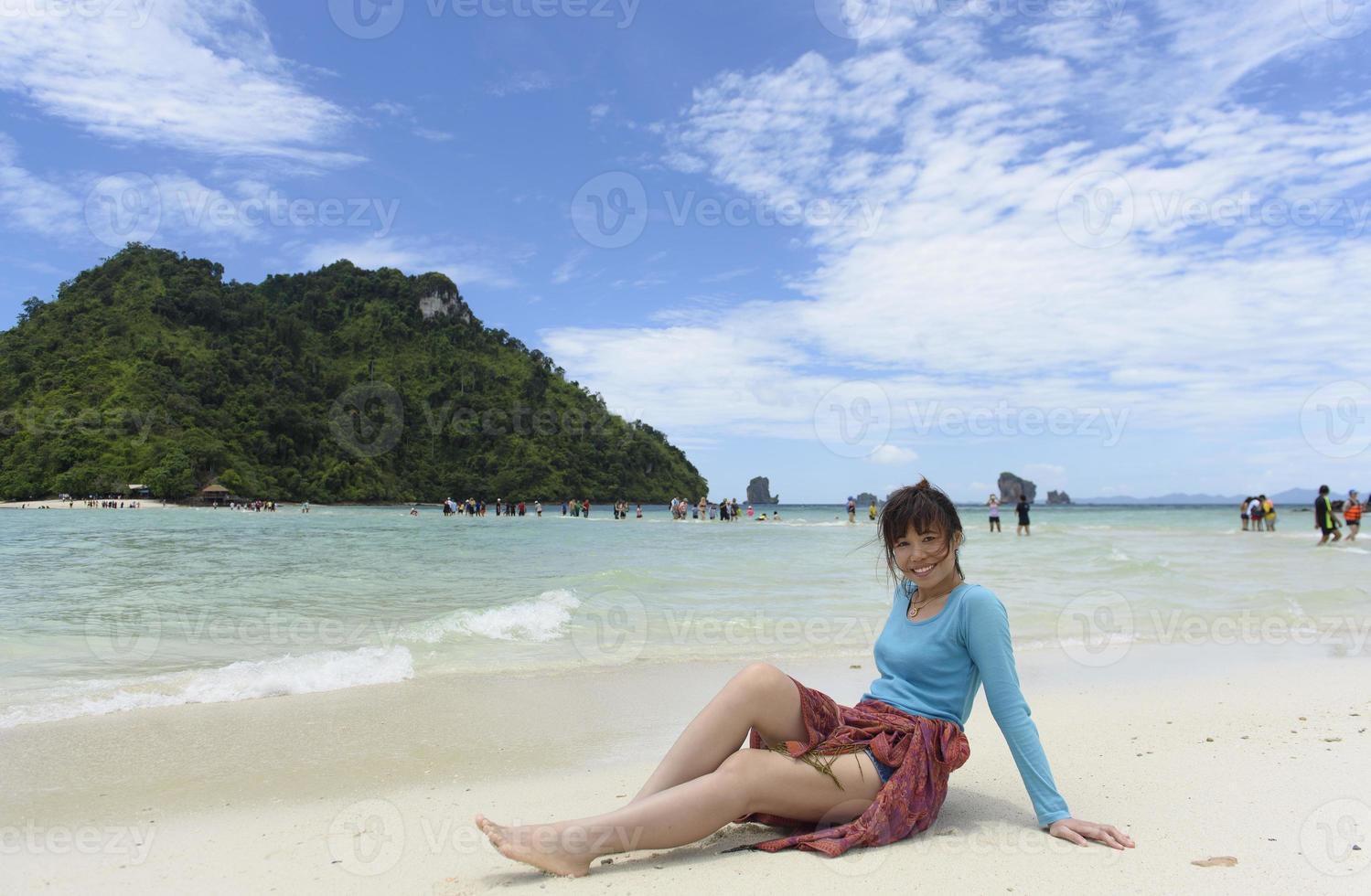 kvinnor tycker om att spela sand på stranden foto