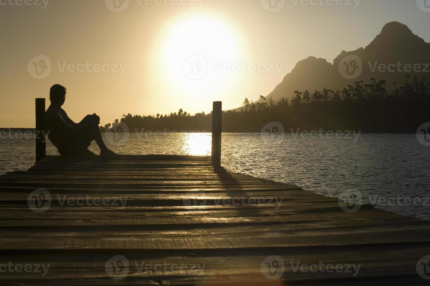 man sitter på kajen vid sjön foto