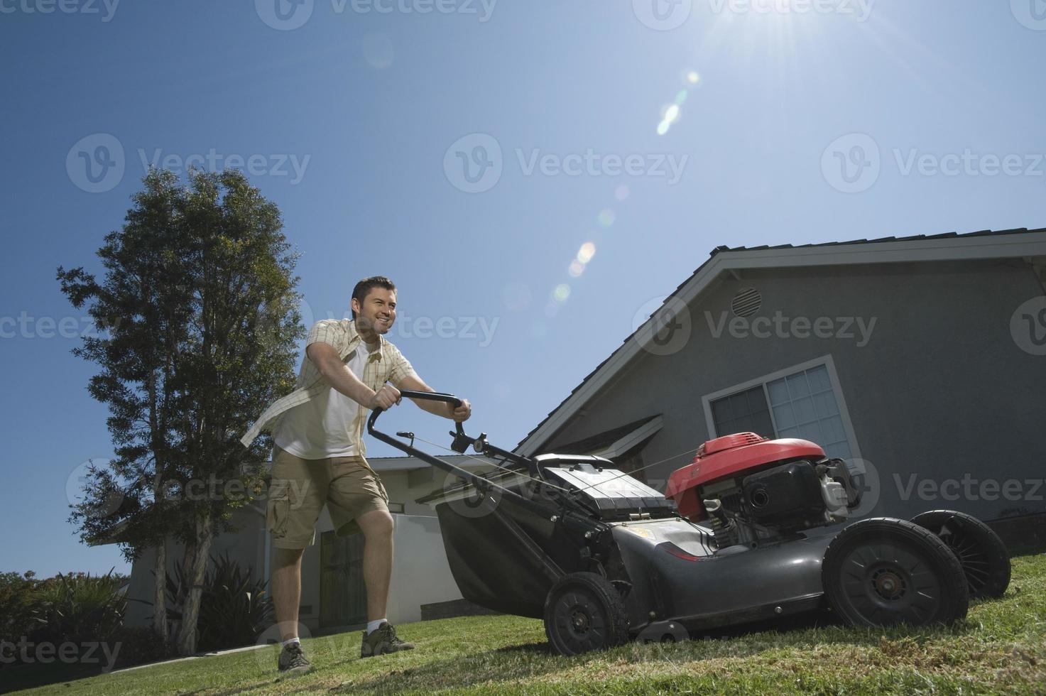 man flyttar gräsmattan foto