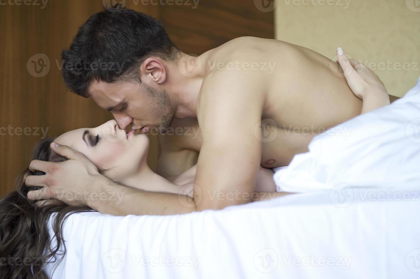 ovanifrån av lekfulla unga par som tycker om i sängen foto
