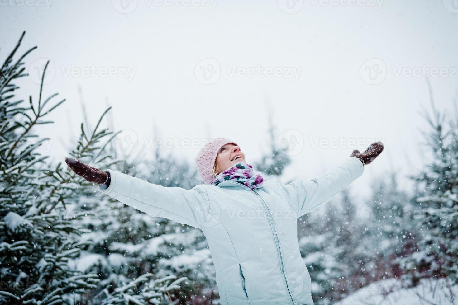glad söt kvinna som tycker om vintern under en snöig dag foto