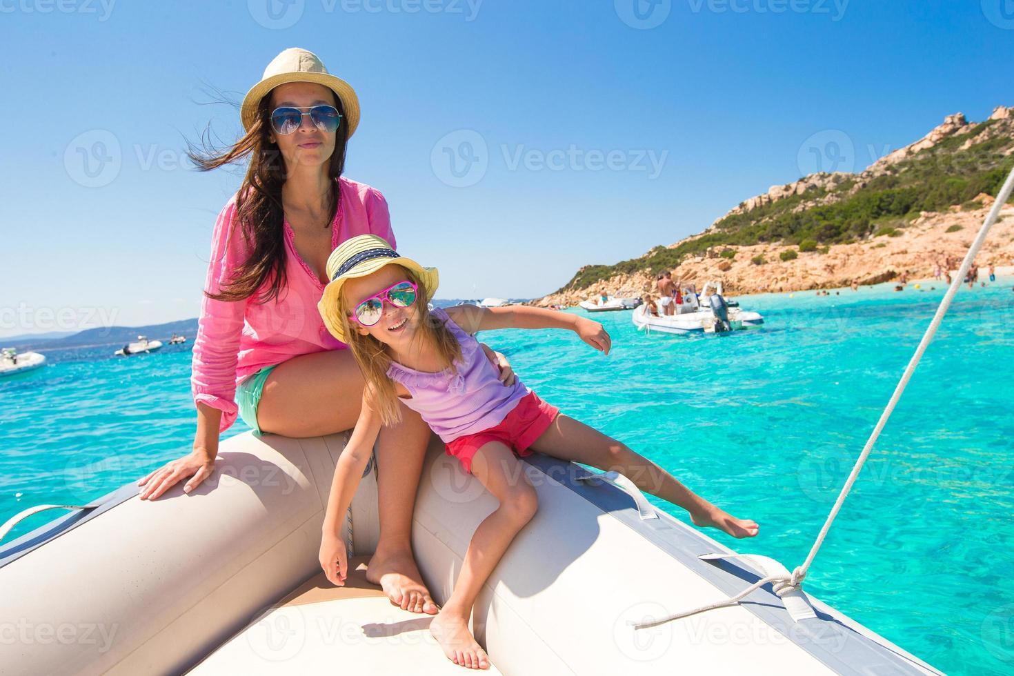 ung mamma med bedårande dotter njuter av semester på båt foto