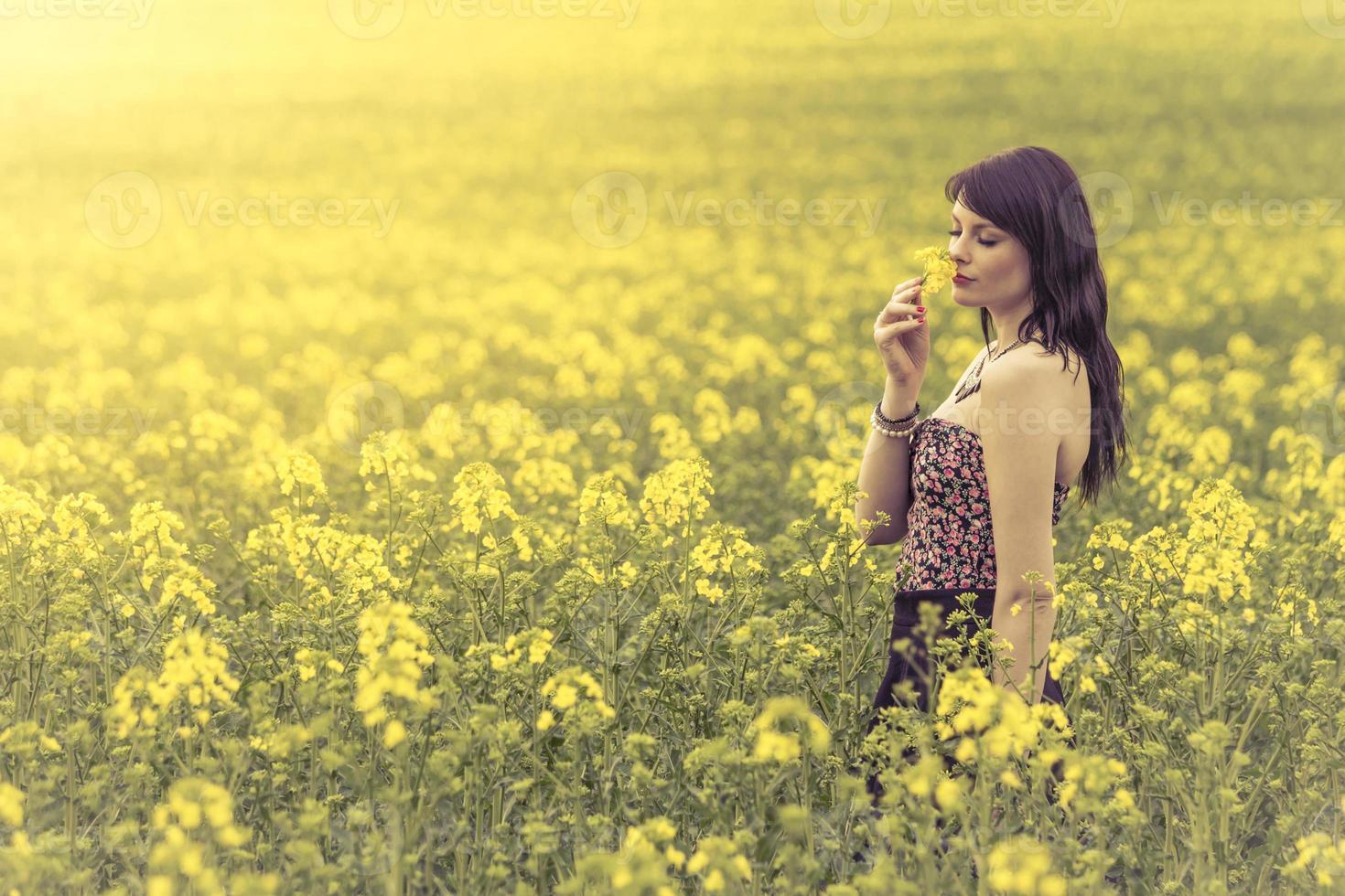 vacker kvinna i äng av gula blommor njuter av blomman foto