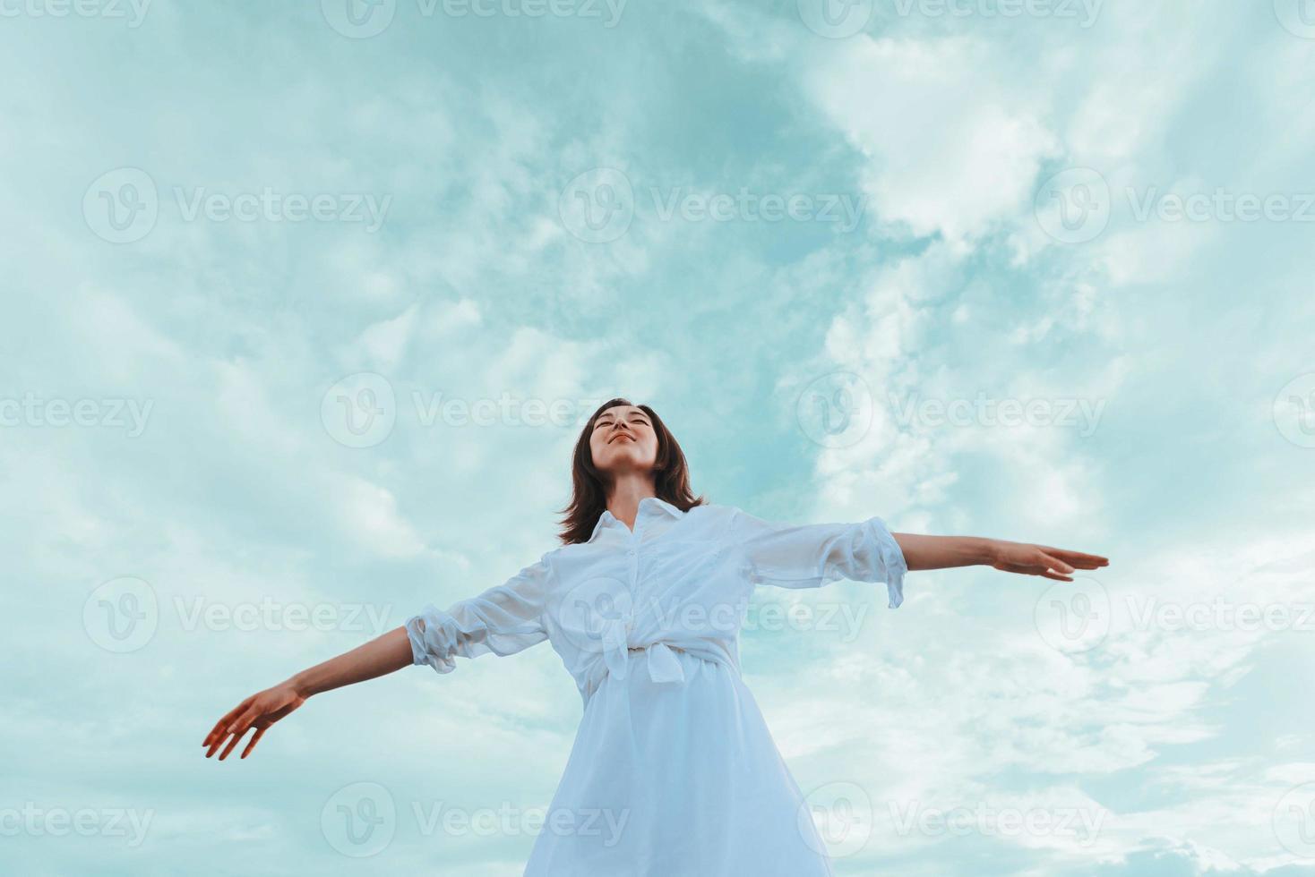 ung kvinna med upphöjda armar njuter av en trevlig dag foto