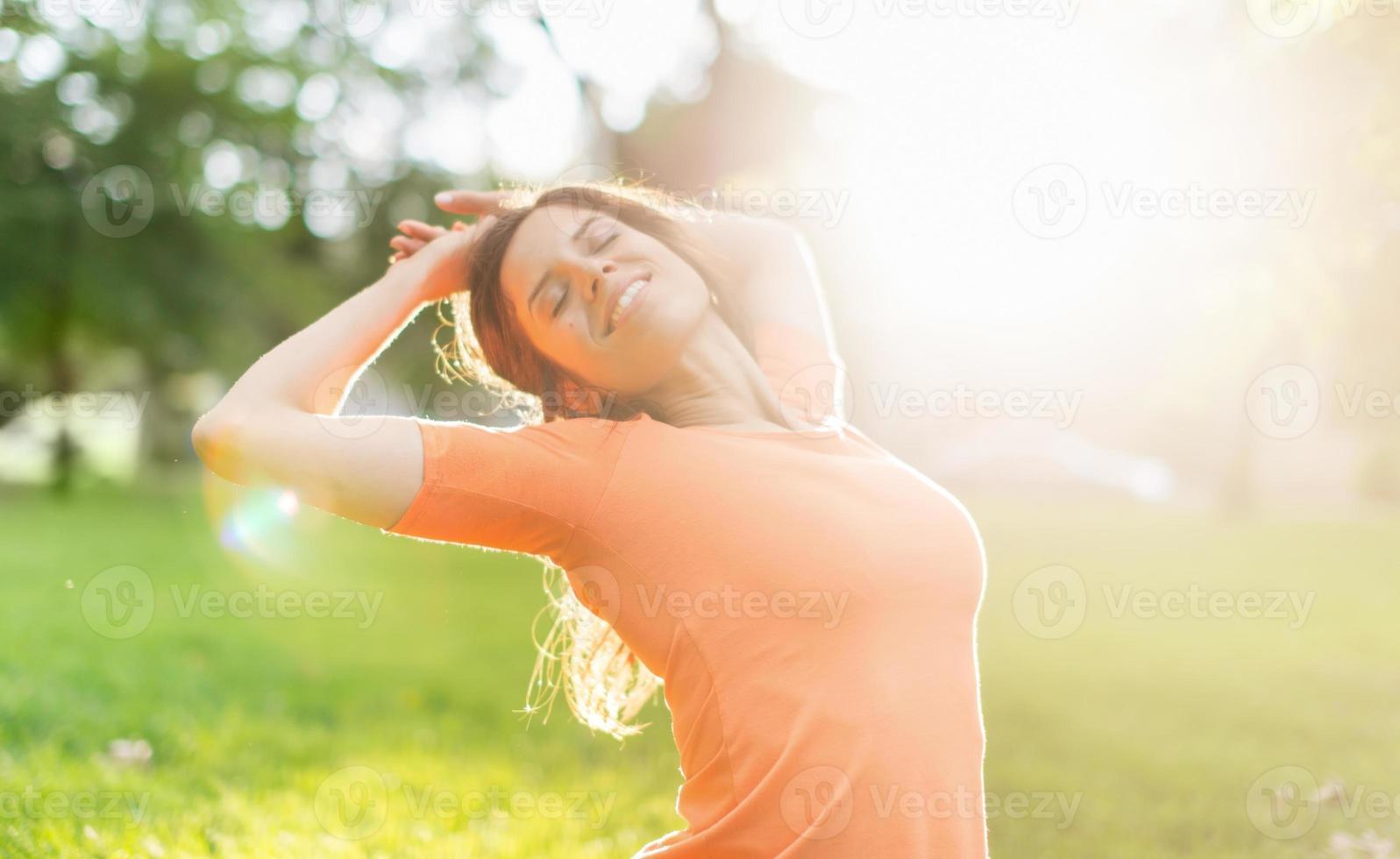 multietnisk tjej som njuter av värmen från en solnedgång foto