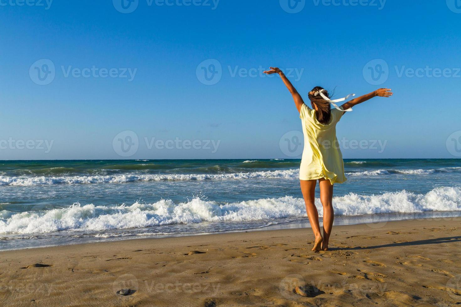 ung kvinna njuter av sin tid på en strand i skymningen foto