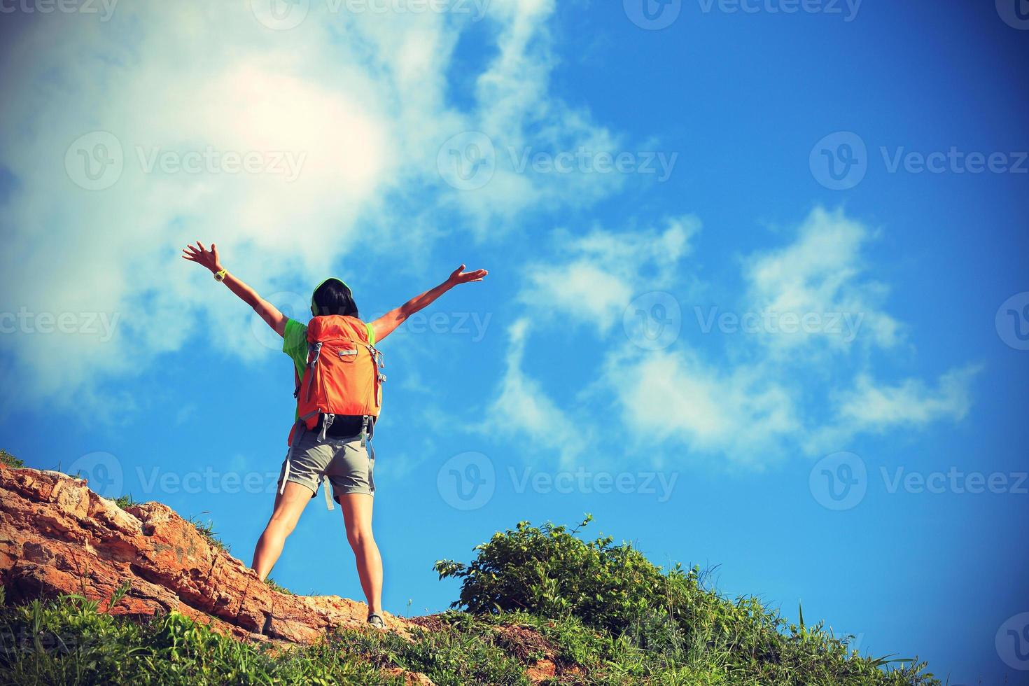 jublande ung kvinna backpacker njuta av utsikten vid bergstoppen foto
