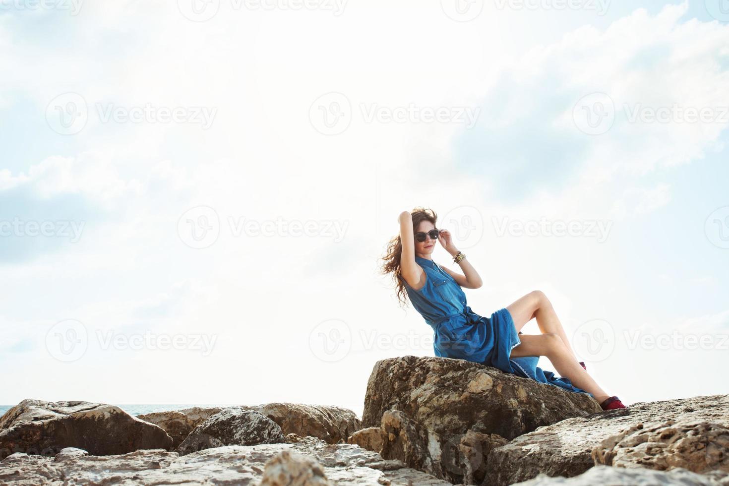 vacker flicka sitter på klipporna foto