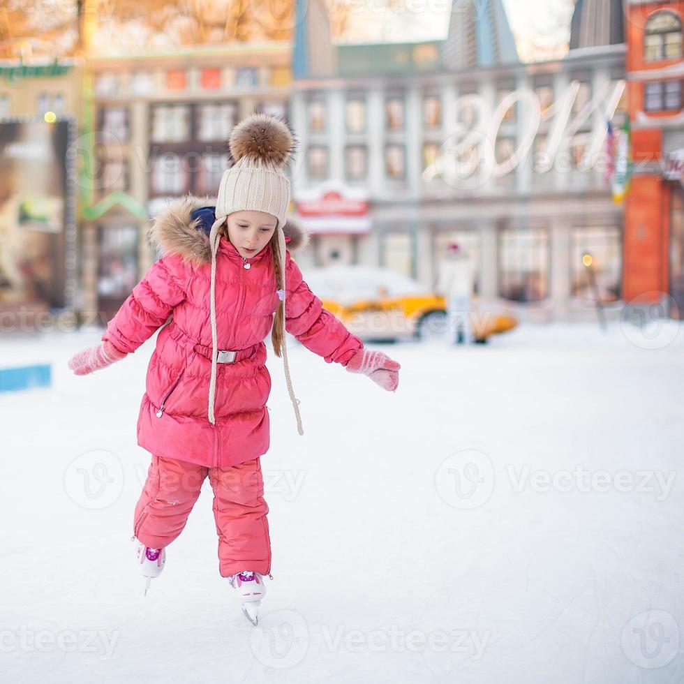 bedårande glad liten flicka som tycker om åka skridskor på isbanan foto
