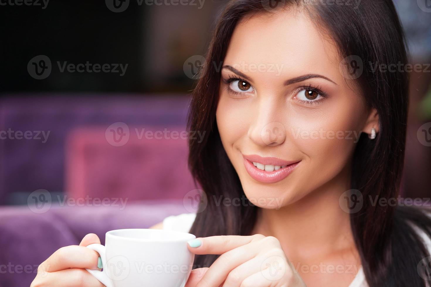 ganska ung flicka njuter av varm dryck i cafeterian foto