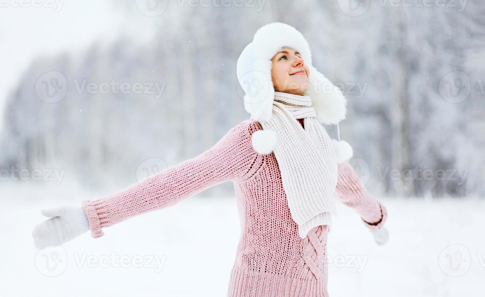 glad kvinna njuter av snöig vinterväder i skogen foto